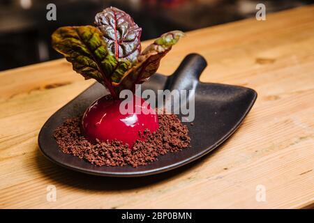 Vanille - Kokos-mousse mit Schokolade und Rote-Bete-Sauce. Dessert in Form von Rüben ist auf eine ungewöhnliche Platte in Form einer Schaufel, serviert. - Stockfoto