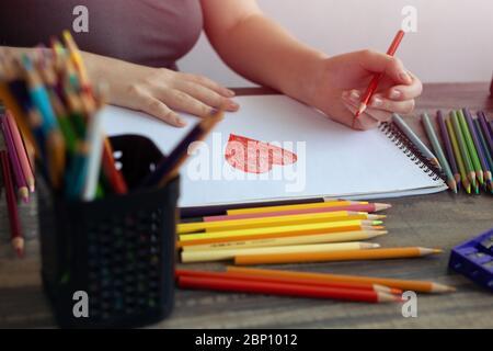 Nahaufnahme der Hände einer Frau, die ein Herz mit Buntstiften auf weißem Papier zeichnen. Arbeitsplatzkonzept des Art Studios - Stockfoto