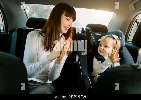 Ziemlich lachende Frau, junge Mutter sitzt in einem Auto, Spaß mit ihrem kleinen Mädchen in einem Kindersitz, klatschen Hände und lächeln. Kind Stockfoto