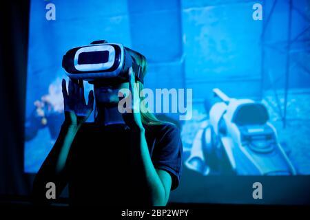 Junge Entwickler von neuen futuristischen Videospiel mit vr Headset gegen großen Bildschirm mit virtuellen Maschinen während der Präsentation stehen - Stockfoto