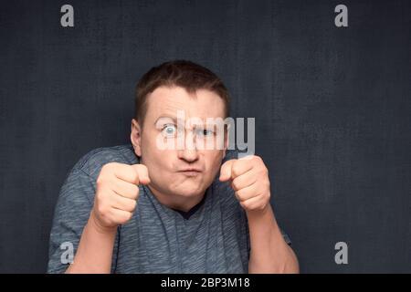 Studio-Nahaufnahme Porträt des unzufriedenen kaukasischen Mann mit barhaarigen Haaren, schaut streng auf die Kamera, Stirnrunzeln Gesicht, hält Fäuste wie Boxer bereit zu kämpfen - Stockfoto