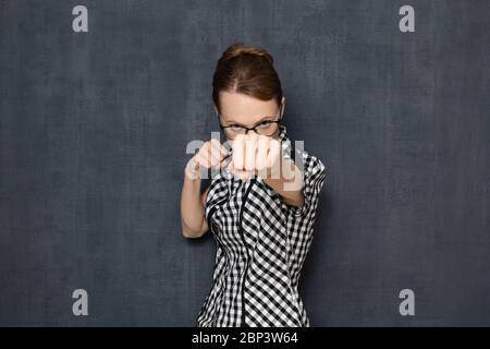 Studio Taille-up-Porträt von fokussierten unzufriedene junge Frau mit Brille, trägt Hemd, hält Fäuste vor ihr geballt, macht Punsch, bereit - Stockfoto