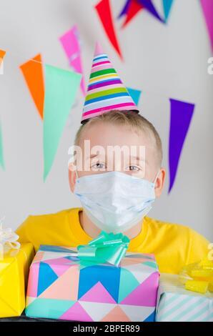 Happy Boy in Medizin Gesichtsmaske und festliche Mütze mit Geschenken in der Hand feiert Geburtstag. Geburtstag allein in Isolation sperren. Soziale Distanz. - Stockfoto