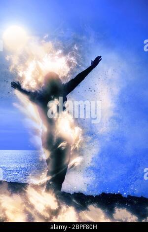 Eine einsame Frau, die ihre Arme geistig Anhebung auf Feuer vor einer mächtigen Welle auf der Klippe - Stockfoto