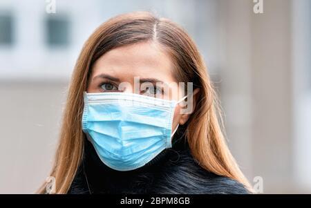 Junge Frau trägt Einweg-blauen Virus Gesicht Mund Nase Maske, Nahaufnahme Porträt. Coronavirus Covid-19 Konzept zur Prävention von Ausbrüchen - Stockfoto
