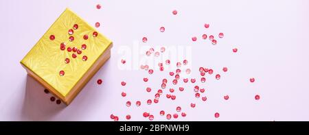 Geschlossene gelbe Geschenkbox mit Party Konfetti auf rosa Hintergrund. Flaches Lay - Stockfoto