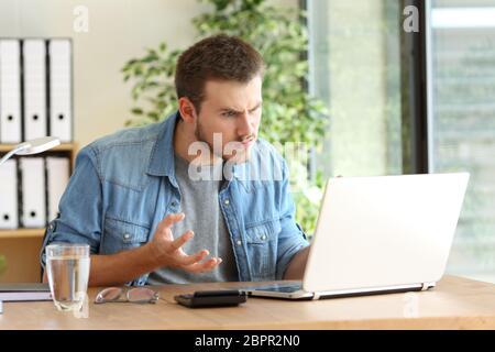 Wütend freiberufliche professionelle Probleme auf Linie mit einem Laptop in einem Desktop neben ein Fenster im Büro - Stockfoto