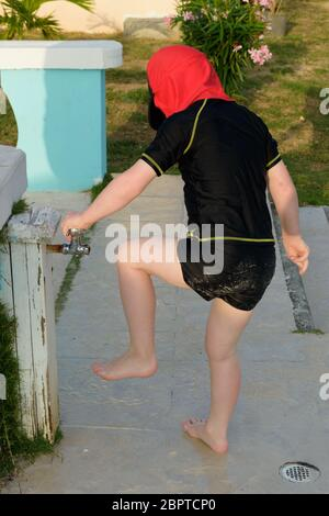 Ein kleines Kind, das nach dem Spielen am Strand den Sand von den Füßen waschen wird - Stockfoto