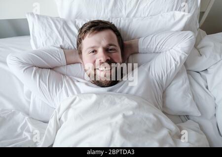 Zufriedener Mann im Schlafanzug liegt im Bett auf einem weichen Kissen mit Händen unter dem Kopf, er ist glücklich und lächelnd. - Stockfoto