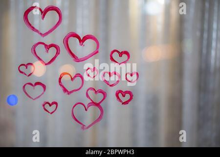 Schönes Mädchen malt ein Herz auf Glas - Stockfoto