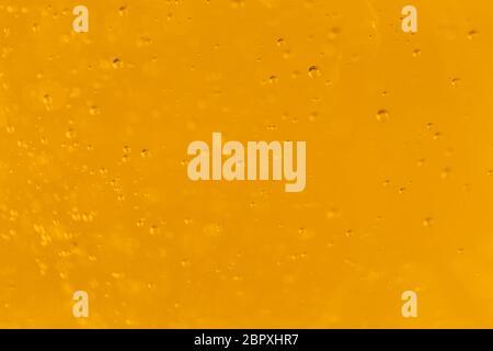 Viele kleine Blasen auf einem orangefarbenen Hintergrund, Makroaufnahme von Flüssigseife, Makroaufnahme von Glas mit Bier, Makroaufnahme von Cocktail mit Fruchtsaft - Stockfoto