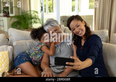 Gemischte Rassenfrau mit ihrer älteren Mutter und ihrer jungen Tochter, die ein Selfie machen