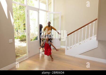 Gemischte Rennpaar und ihre junge Sohn und Tochter zu Hause ankommen Stockfoto