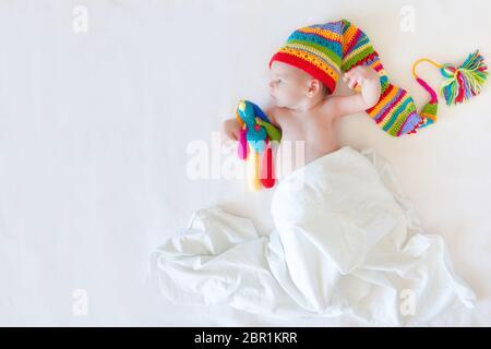 Ein Junge in weißen Kleidern liegt auf einer weißen Windel. Eine helle farbige Kappe. Pinsel auf den Hut. - Stockfoto