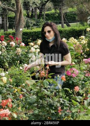 Junge Frau spazierengeht in einem Rosengarten mit Maske - Stockfoto