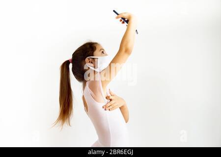 Liebenswert kleines Mädchen im Gesicht Maske verlängern Arm halten Handy Selfie mit, weiße Wand Hintergrund. Online-Chating und Fernunterricht während - Stockfoto