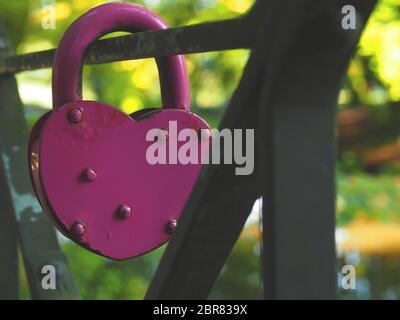 Alten rostigen Rosa herzförmige Vorhängeschloss auf eine Stahlbrücke, aus nächster Nähe erschossen, konzeptionelle Liebe Hintergrund