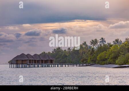 Sonnenuntergang Himmel und Reflexion über das ruhige Meer, Malediven Strand Landschaft von Luxus über Wasser Bungalows. Exotische Landschaft von Sommer und Urlaub