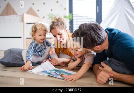 Junge Familie mit zwei kleinen Kindern im Schlafzimmer ein Buch lesen. Stockfoto