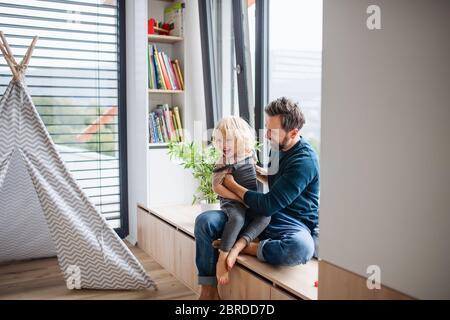 Vater mit kleinen Jungen, der drinnen im Schlafzimmer spielt, spielt.