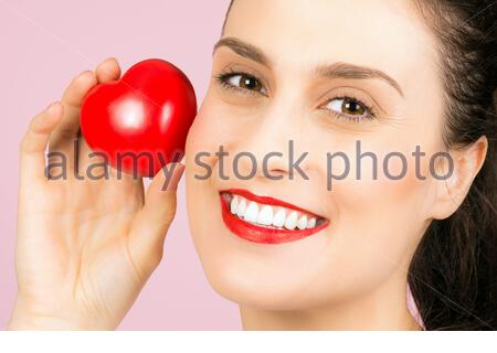 Die lächelnde schöne Frau mit roten Lippen hält auf rosa Hintergrund ein kleines rotes Herz in der Hand. - Stockfoto