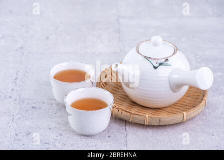 Heißer Tee in weißer Teekanne und Tassen auf einem Sieb über hellgrauen Zement Hintergrund, Nahaufnahme, kopieren Raum Design-Konzept. - Stockfoto