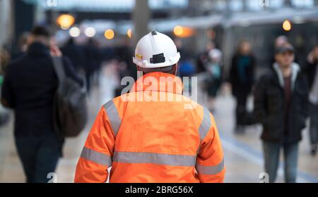 Arbeiter, der durch einen Bahnhof in England, Großbritannien läuft. Stockfoto