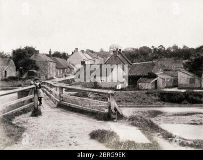 Dorfszene - Nunnington in Yorkshire mit hölzerner Fußgängerbrücke über den Fluss - Stockfoto
