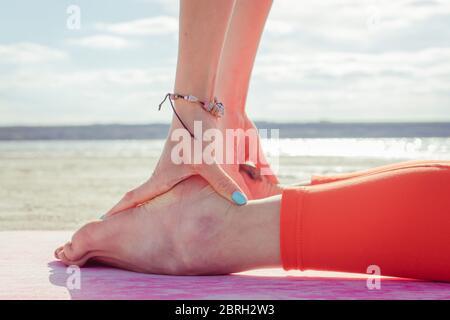 Nahaufnahme. Junges Mädchen in roten Leggings tun Stretching und Übungen von Pilates im Freien im Sommer. Fitness Yoga Stretching Training draußen. Gesund l - Stockfoto
