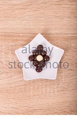 Schokolade Kugeln auf einem sternförmigen Ceramic White Untertasse, auf einer hölzernen Hintergrund. - Stockfoto