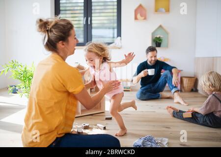 Junge Familie mit zwei kleinen Kindern im Schlafzimmer spielen.