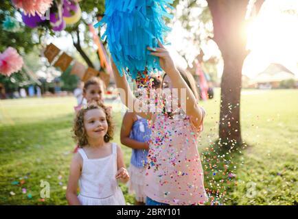Kleine Kinder im Freien im Garten im Sommer, spielen.