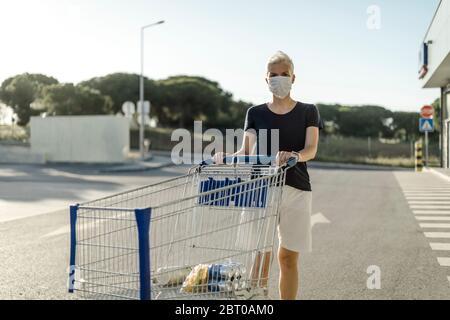 Frau mit schützender Gesichtsmaske mit Warenkorb vor dem Supermarkt - Stockfoto