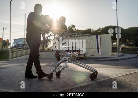 Vater schiebt den Einkaufswagen mit seinem kleinen Sohn auf einen Parkplatz. Beide tragen Schutzmasken. - Stockfoto
