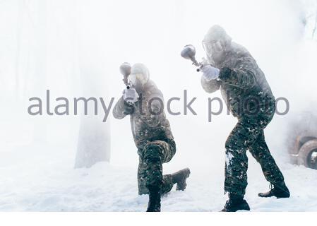 Zwei paintball Spieler in Uniform und Masken auf den Feind schießen, Seitenansicht, Winter Forest Kampf. Extreme Game - Stockfoto