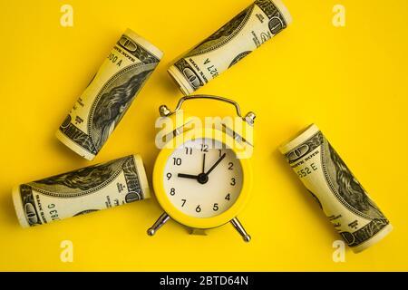 wecker beide Geldwerte Dollar, Zeit ist Geld. Retro-Wecker und Hundert-Dollar-Rechnungen auf gelbem Hintergrund