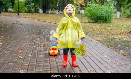 Kleiner Junge in Regenmantel und Gummistiefeln, der auf den regnerischen Himmel im Park schaut - Stockfoto