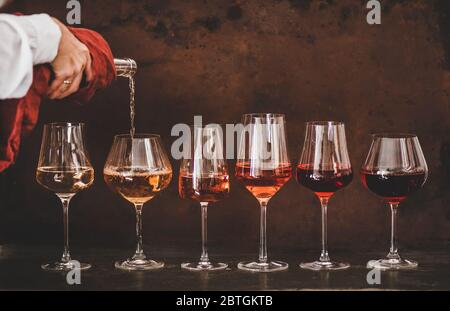 Roséwein in Gläsern und Womans Hand Ausgießen Wein - Stockfoto
