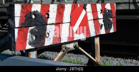 Bahnpuffer Stop mit stark abgenutztem Holz in rot-weiß gestrichenen Streifen mit rot-weißem Stoppschild tagsüber - Stockfoto