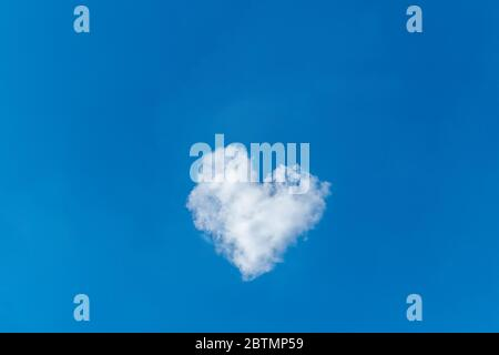 Romantische Wolke in Form eines Herzens auf einem blauen Himmel. Liebeskonzept.