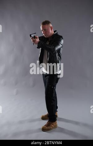 Isoliertes Bild eines Mannes mit einer Waffe, der eine schwarze Lederjacke trägt. Ideal für Undercover- oder Detektivanwendungen wie Buch- und eBook-Cover-Design. - Stockfoto