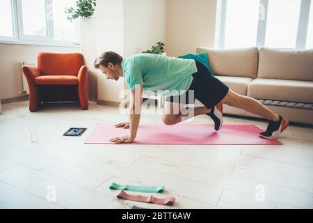 Kaukasischer Mann, der Sport-Übungen zu Hause macht, während er auf die Tablette auf dem Boden schaut - Stockfoto