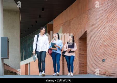 Drei asiatische Studenten gehen in der Universitätshalle während der Pause an der Universität zu Fuß und reden zusammen. Bildung, Lernen, Student, Campus, Universität, - Stockfoto