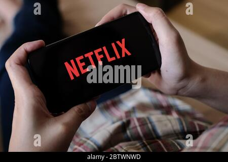 CHIANG MAI, THAILAND, 29. MÄRZ 2020: Frau Hand hält Smartphone mit Netflix-Logo auf Apple iPhone XS zu Hause. - Stockfoto