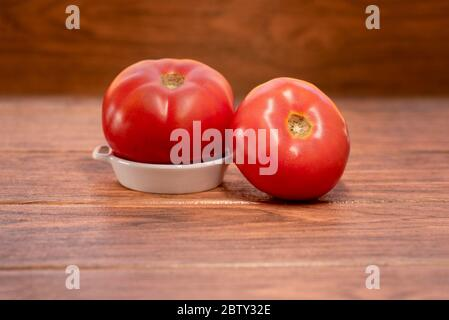 Zwei frische große rote Tomate auf einem weißen Keramikplatte mit Holzhintergrund - Stockfoto