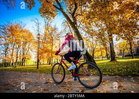 Urban Biken - Frau Reiten Fahrrad im City Park Stockfoto
