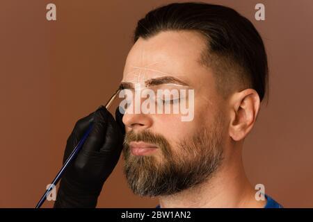 Dauerhafte Make-up für Augenbrauen. Färben von Brauen. Schöner Mann mit Augenbrauen im Friseur. Schönheitsverfahren. Brutal männlich mit Bart bekommt Brauenkorrektur Verfahren. Friseur bei der Arbeit. Brauenpflege Konzept - Stockfoto
