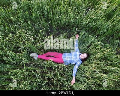 Ein Teenager-Mädchen liegt im grünen Gras bei Sonnenuntergang, Draufsicht, Wandern und Einheit mit der Natur - Stockfoto