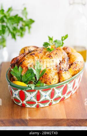 Ganze gebratene Hähnchen mit frischer Petersilie und Zitronenstücke in einem festlichen Gericht - Stockfoto