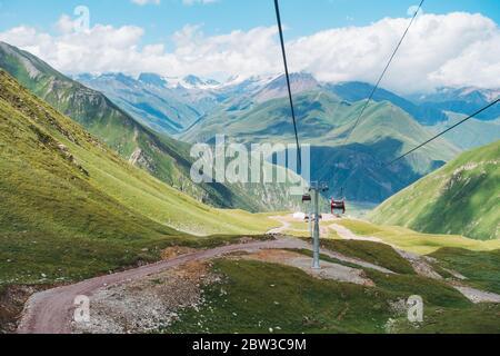 Sommer Blick auf die Kaukasus-Landschaften von der 7,5 km langen Seilbahn Kobi-Gudauri, die die Skigebiete Kobi und Gudauri verbindet. Eröffnet im Januar 2019, Poma Equipment - Stockfoto
